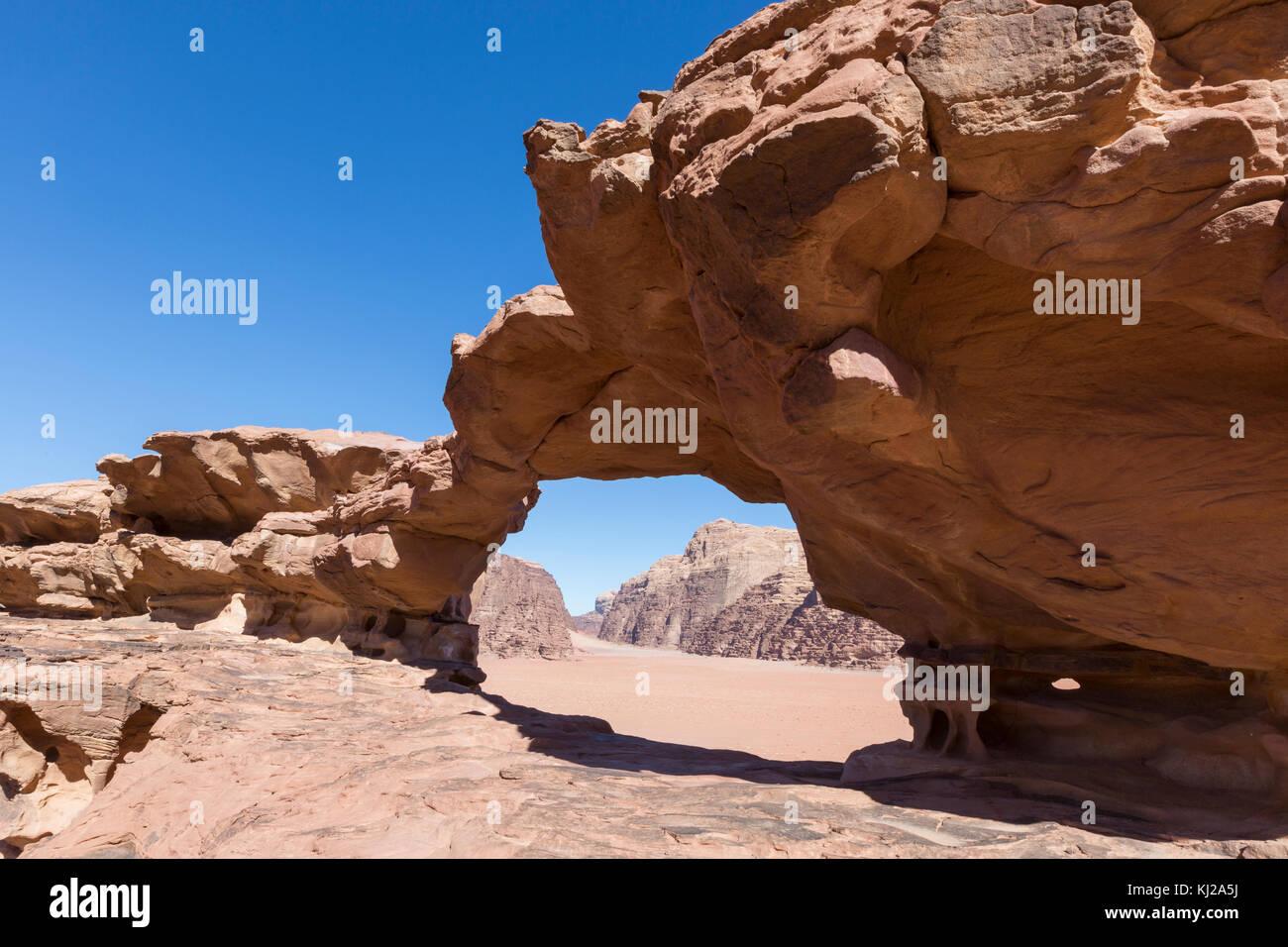 natural rock bridge and panoramic view of Wadi Rum desert, Jordan - Stock Image