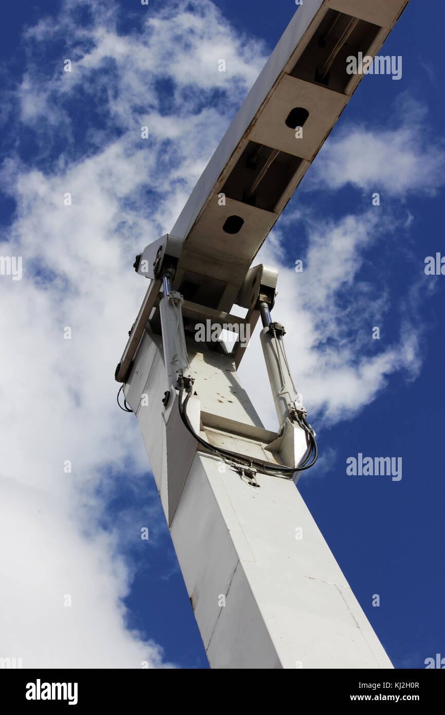 metal steel hydraulic piston to working excavator on a blue sky background. - Stock Image