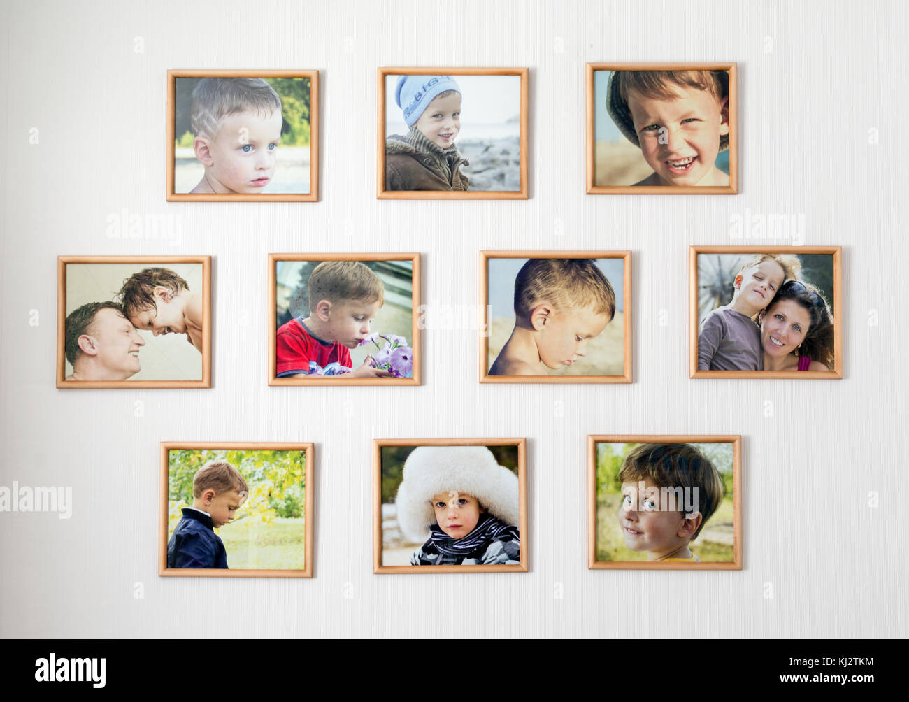 white wall with photos of the family in wooden photo frames - Stock Image