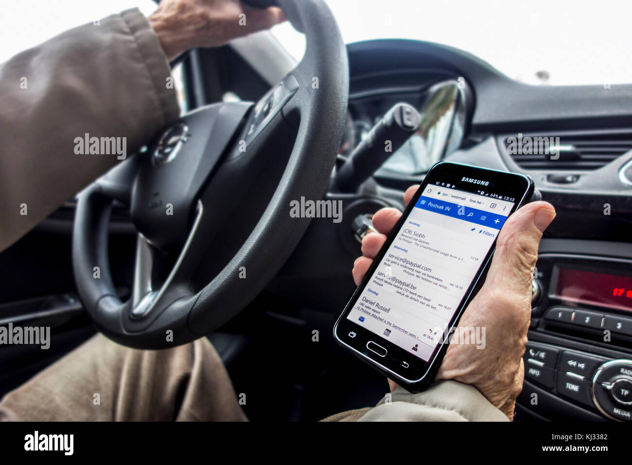 Irresponsible man at steering wheel checking messages on smart phone / smartphone / cellphone while driving car Stock Photo