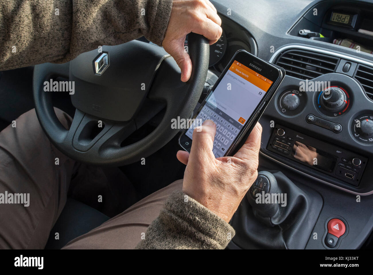Irresponsible man at steering wheel sending message by text messaging / texting on smart phone / smartphone / cellphone - Stock Image