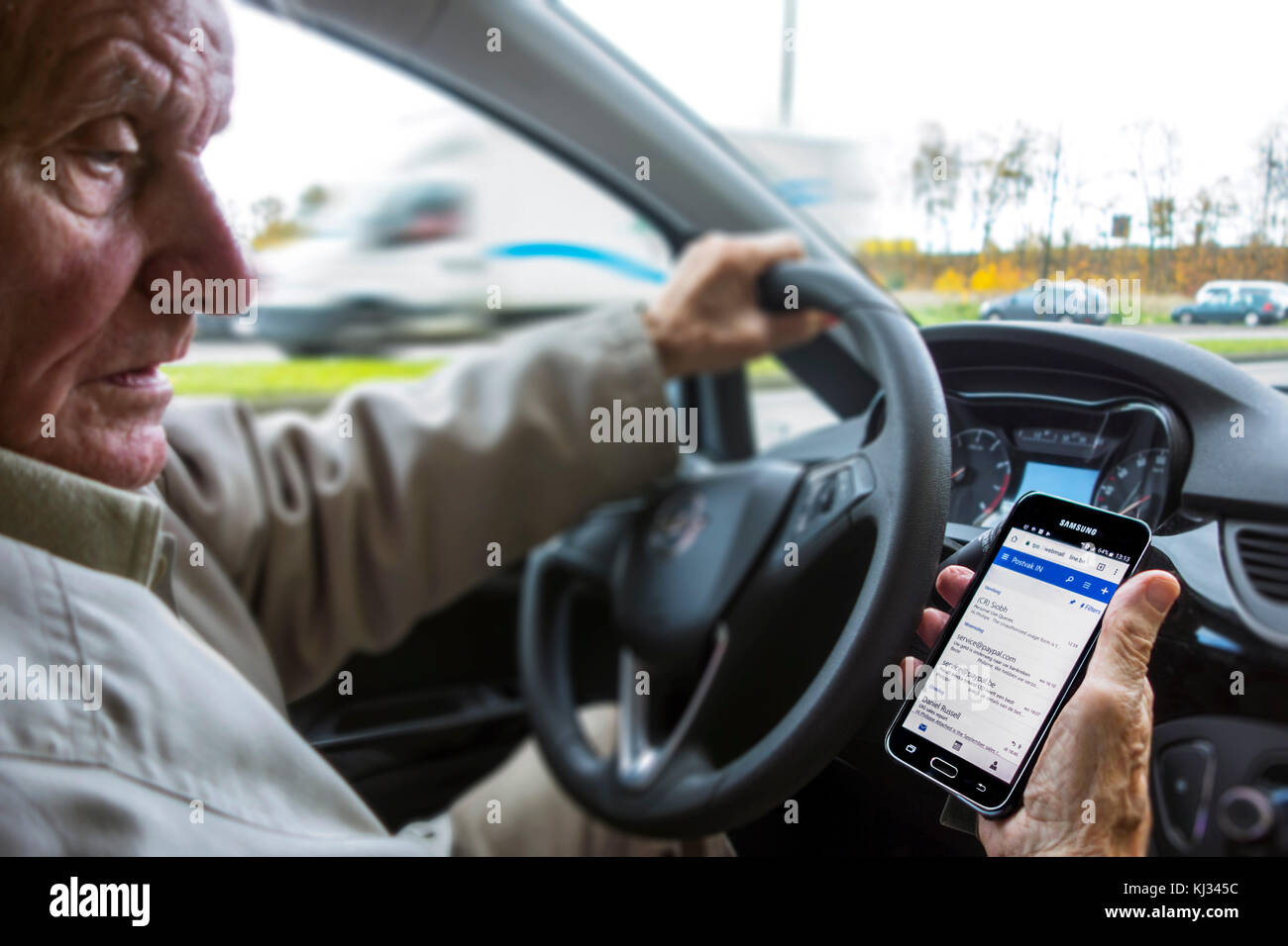 Irresponsible elderly man at steering wheel checking messages on smart phone / smartphone / cellphone while driving - Stock Image