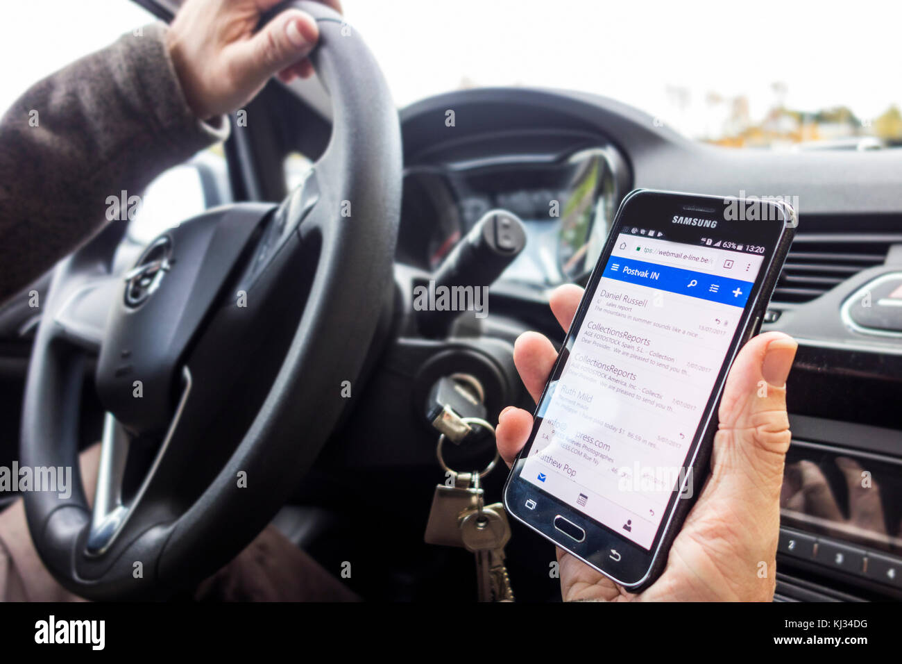 Irresponsible man at steering wheel checking messages on smart phone / smartphone / cellphone while driving car - Stock Image