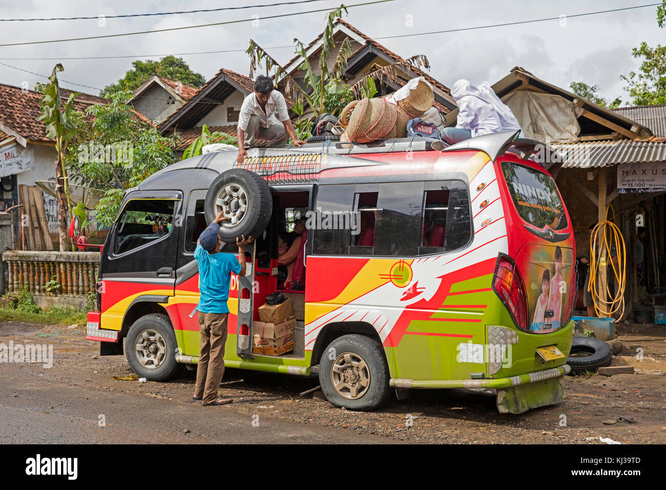 Minibus from Labuan to Tamanyaya being loaded, public transport in Java, Indonesia - Stock Image