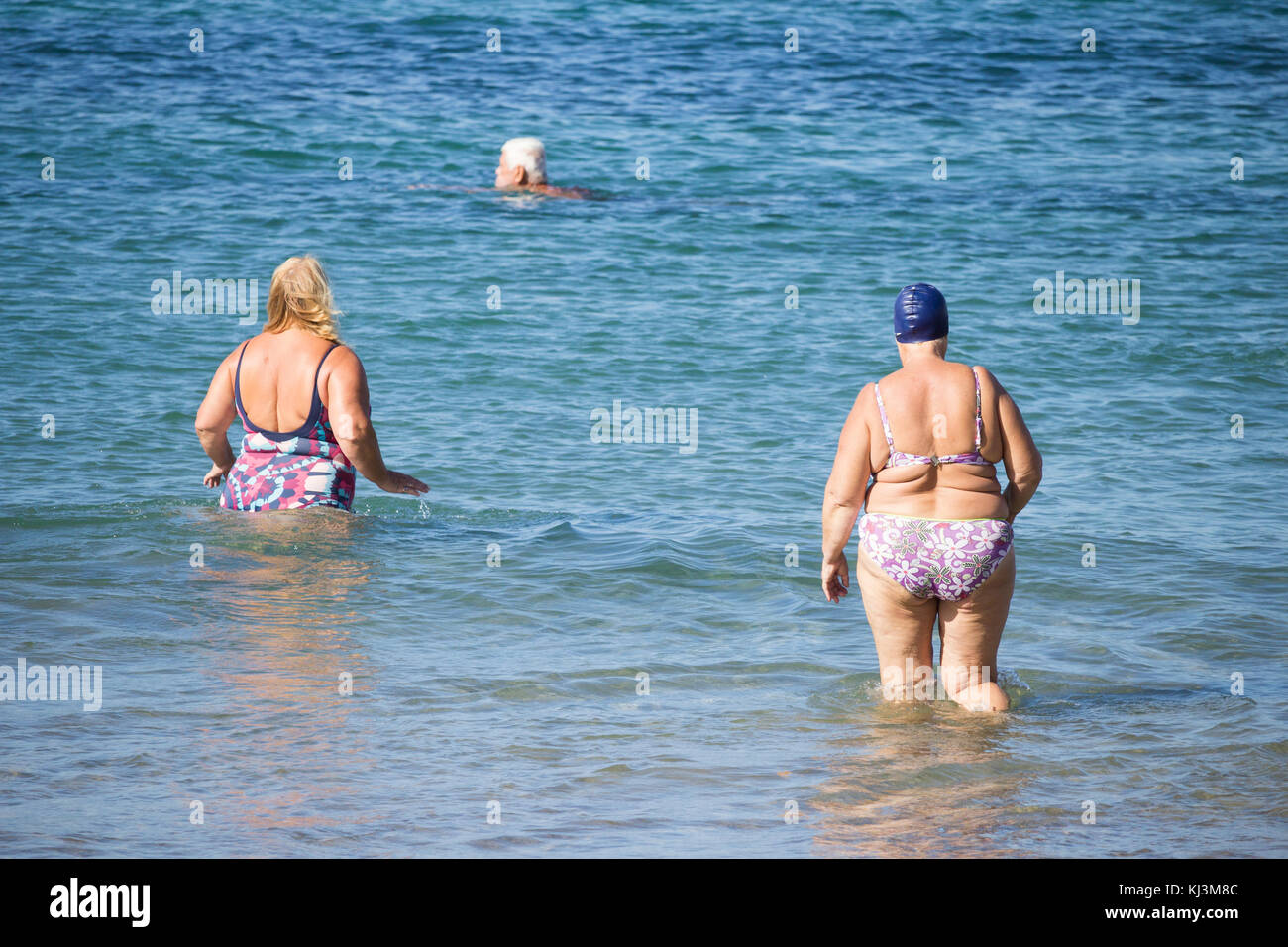 Rear view of elderly women going for swim following daily keep fit class on beach in Spain - Stock Image
