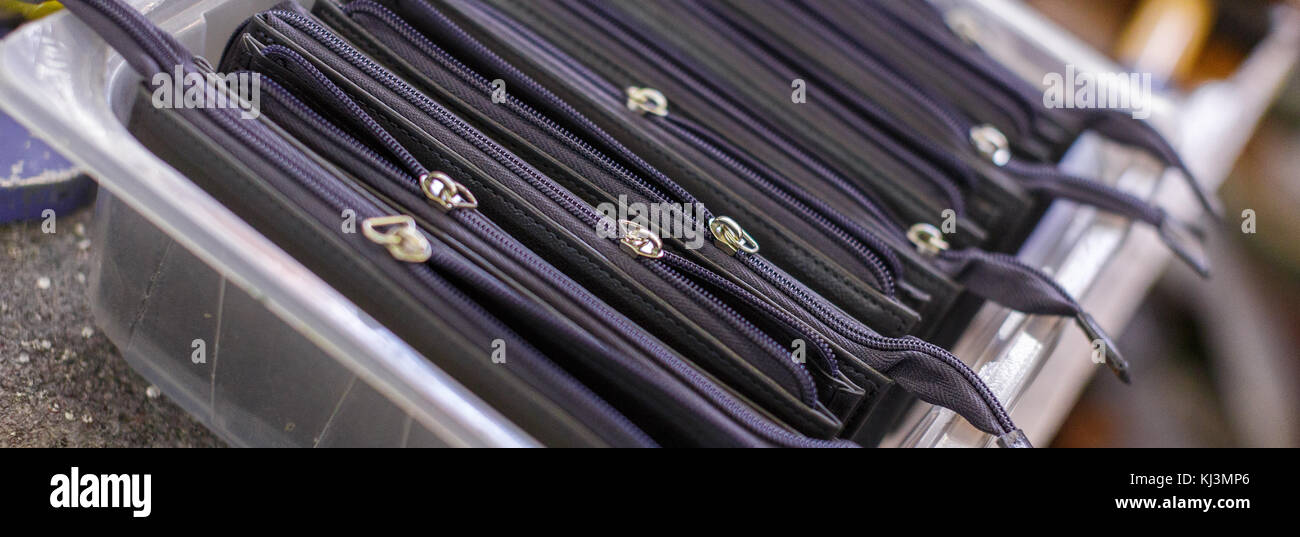 close-up of black purses with zippers in a plastic container. - Stock Image