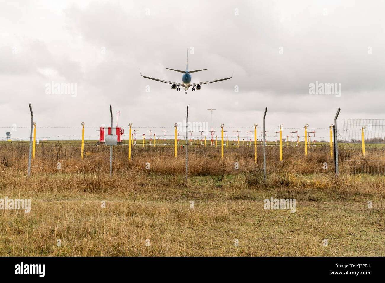 Landing of a large civil aircraft over the landing lights of the airfield, rear view - Stock Image