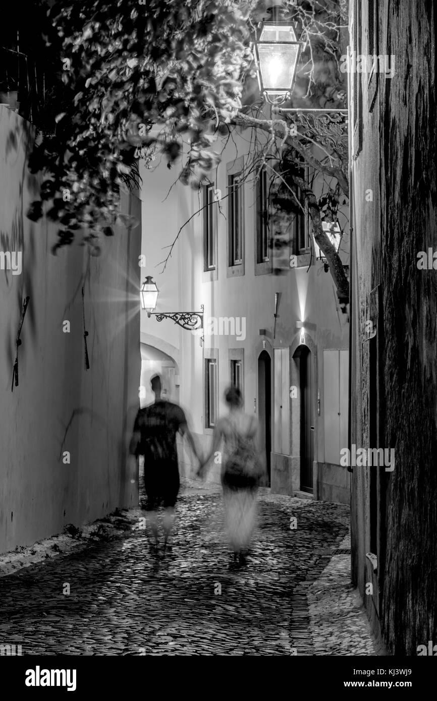 Couple Strolling down street, Lisbon, Portugal - Stock Image