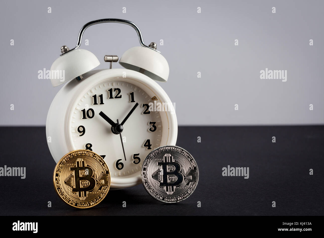Two bitcoins and vintage alarm clock with copy spaces. Cryptocurrency is the future concept - Stock Image