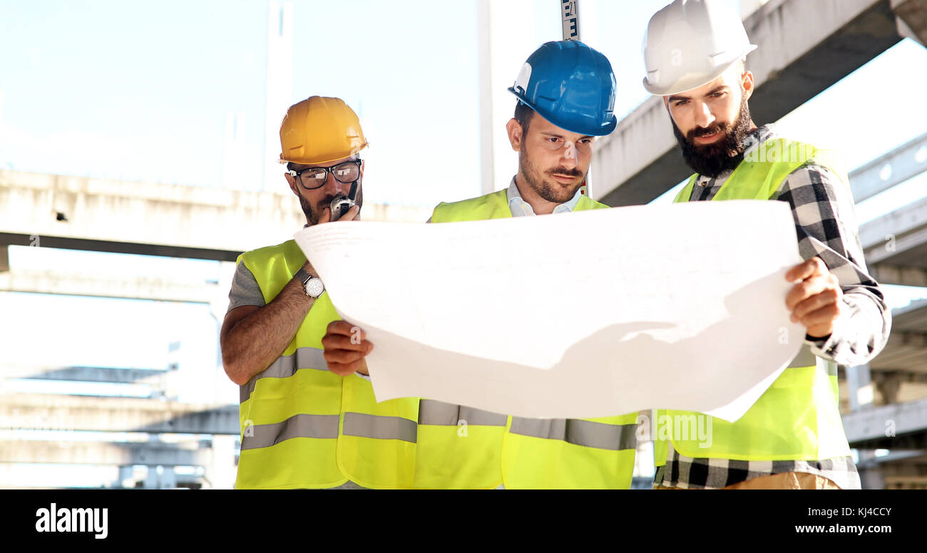 Construction engineers discussion with architects at construction site Stock Photo