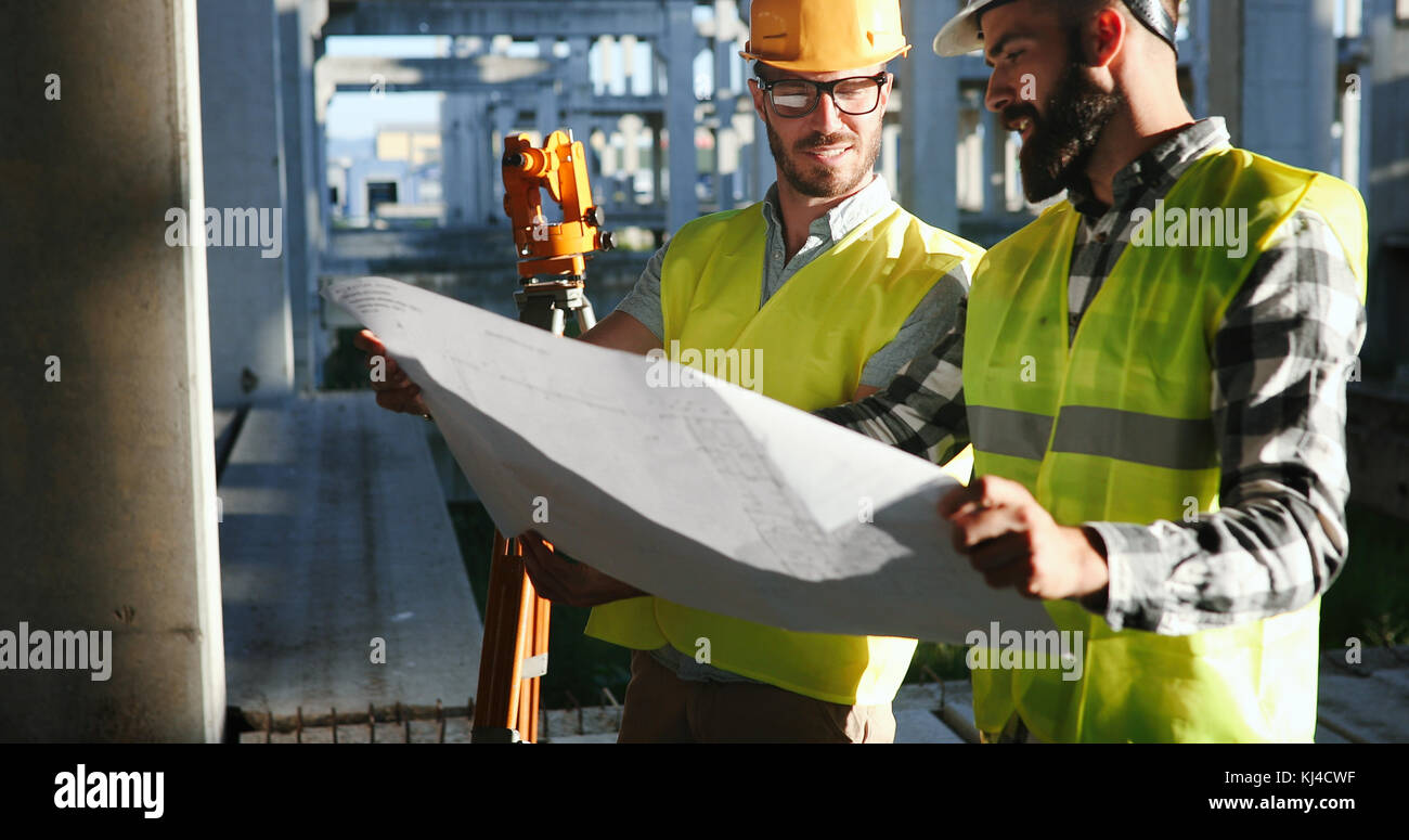 Team of construction engineers working on building site - Stock Image