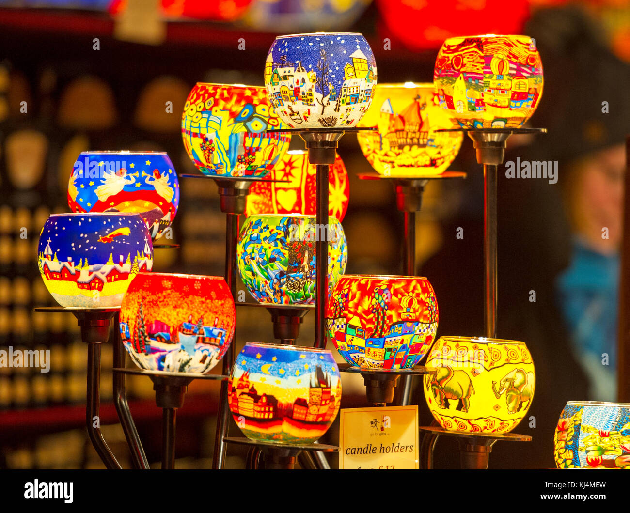 A display of coloured glass candle holders on display at a stall in the Edinburgh Christmas market. - Stock Image