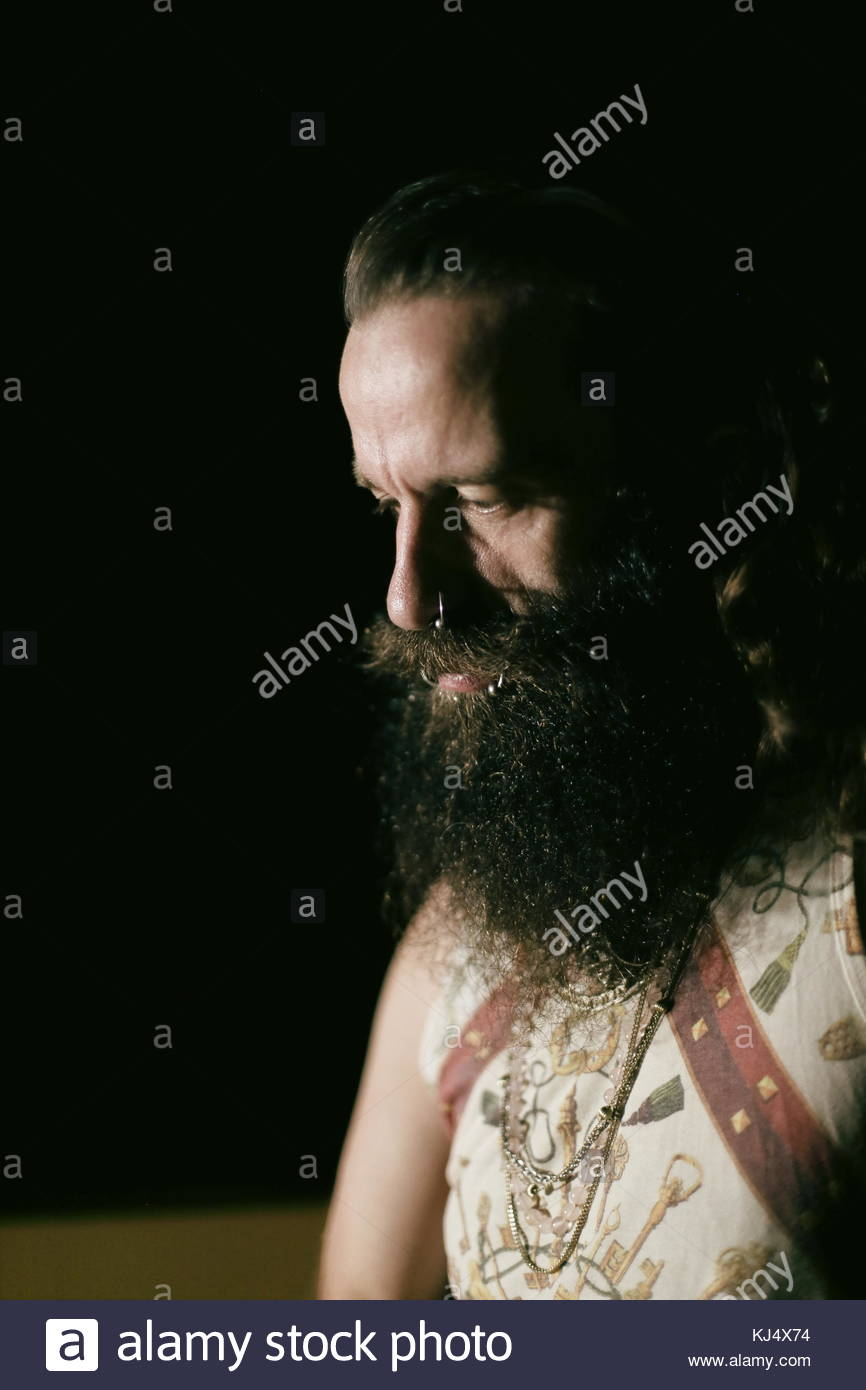 Portrait of a strong big man with long beard and piercings - Stock Image