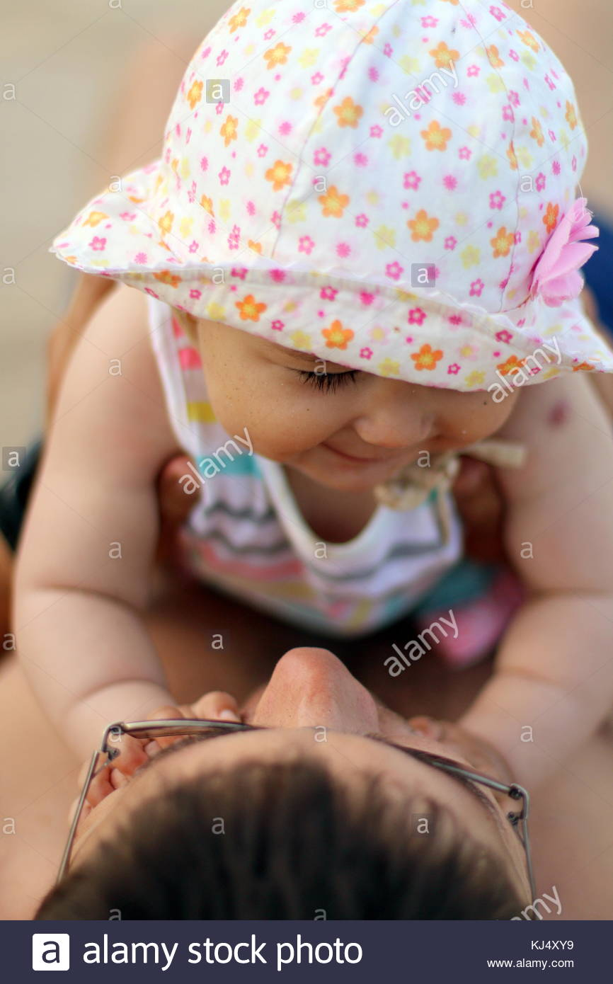 Little baby girl playing with her dad's face - Stock Image