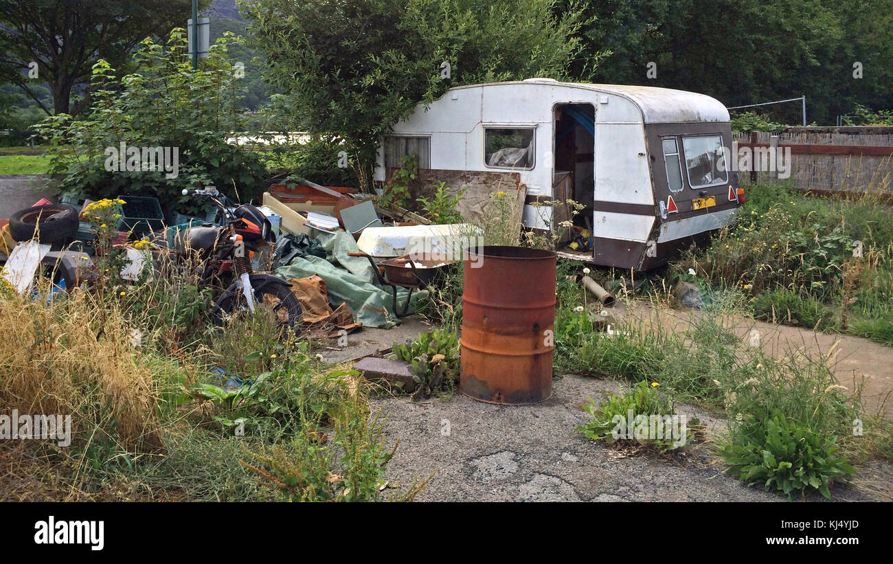 An old derelict abandoned caravan and motorbike plus other bits of rubbish on a piece of overgrown land. - Stock Image