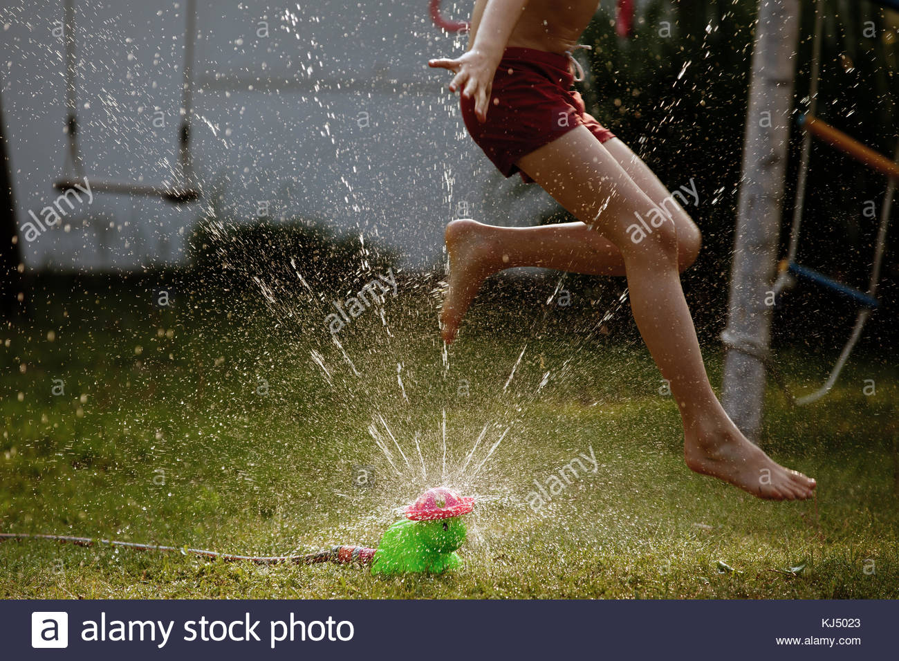 Lawn sprinkler happiness - Stock Image