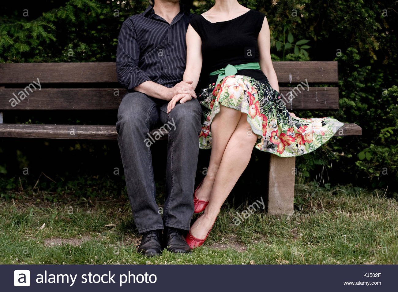 Elegant couple holding hands sitting on a bench - Stock Image