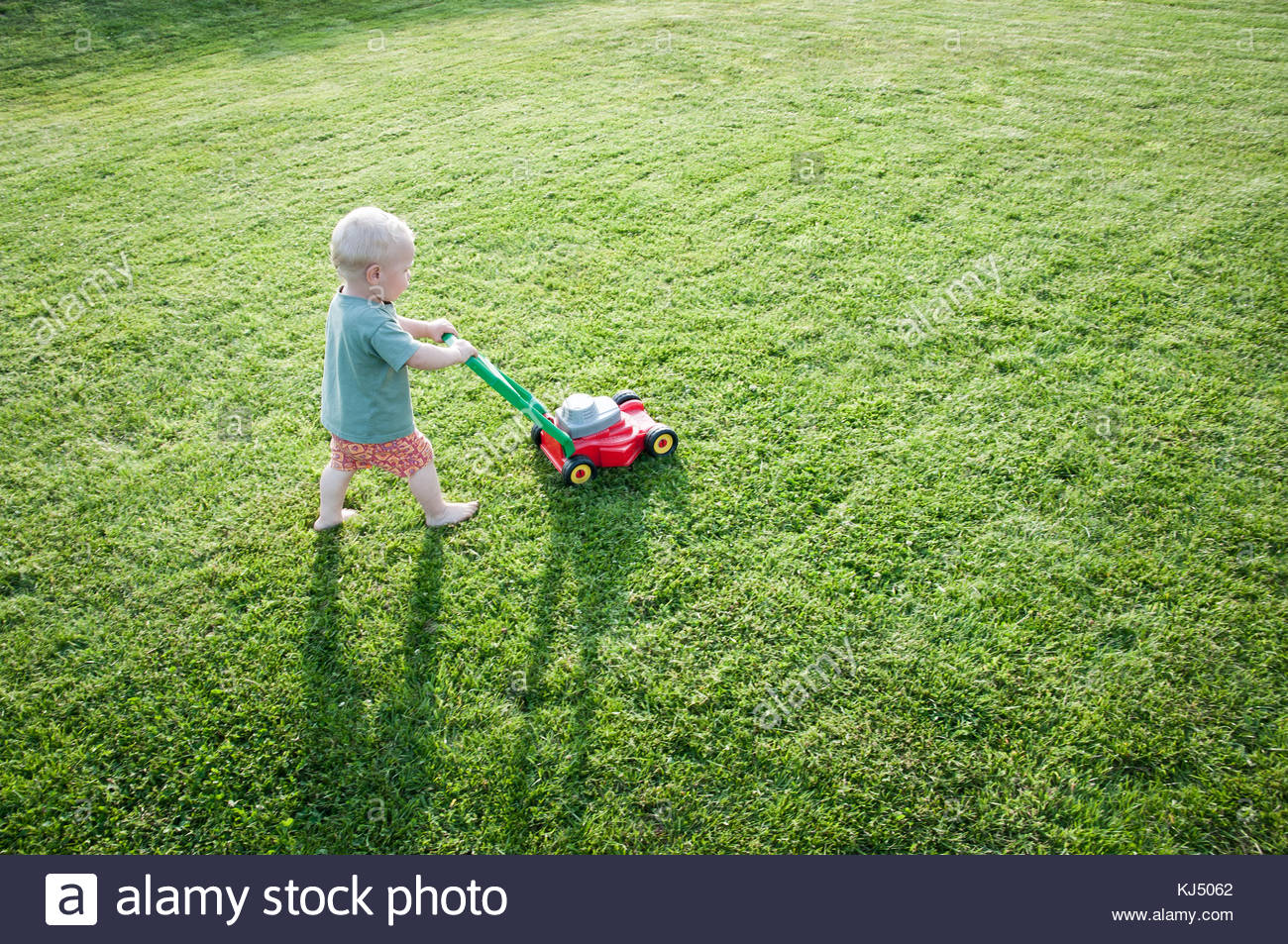 Baby boy with lawn mower - Stock Image