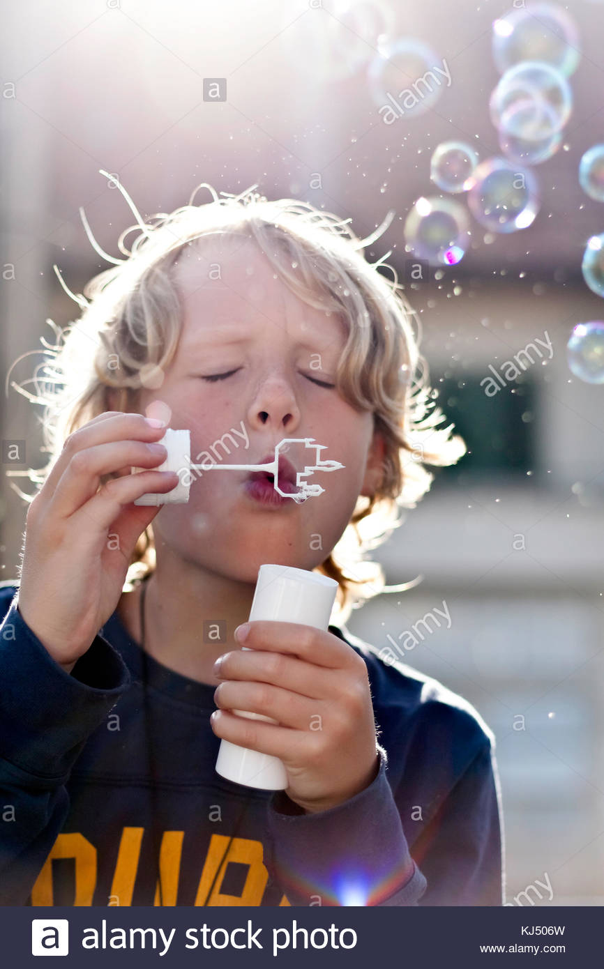 Young boy blowing soap bubbles - Stock Image