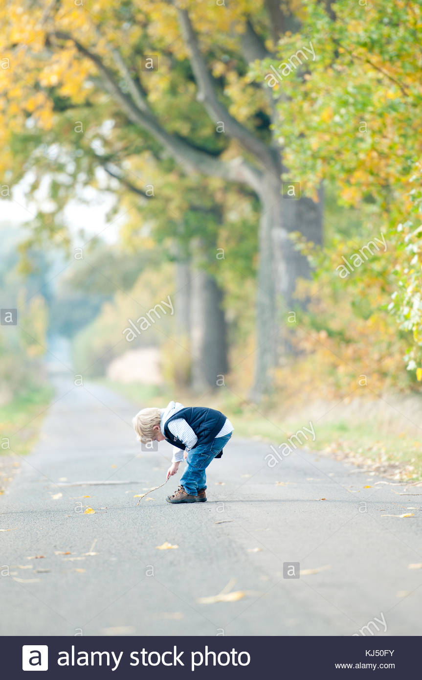 boy bending over on road - Stock Image