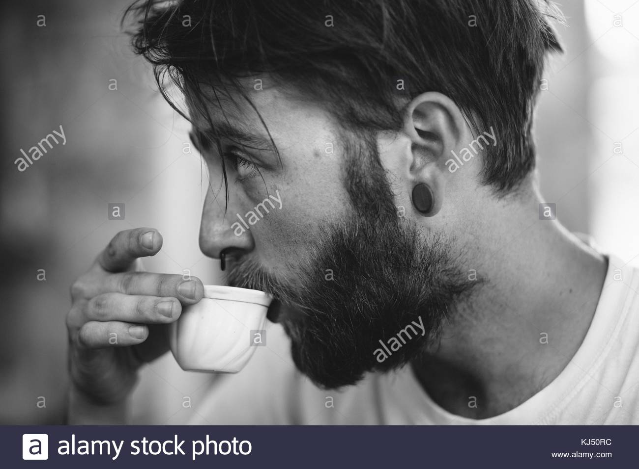 Bearded man with septum piercing drikning coffee - Stock Image