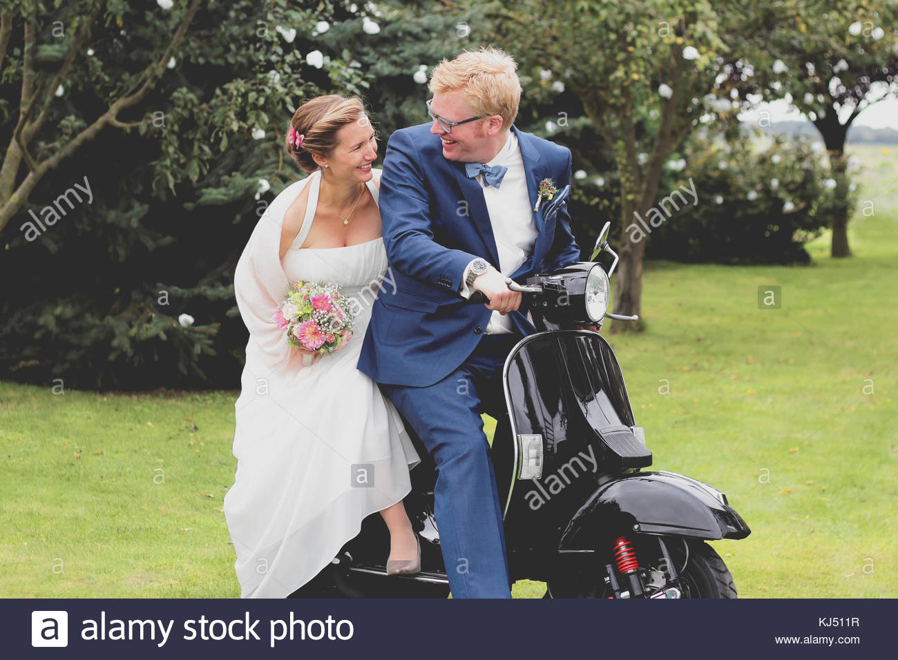 Happy couple on a scooter on their wedding day - Stock Image