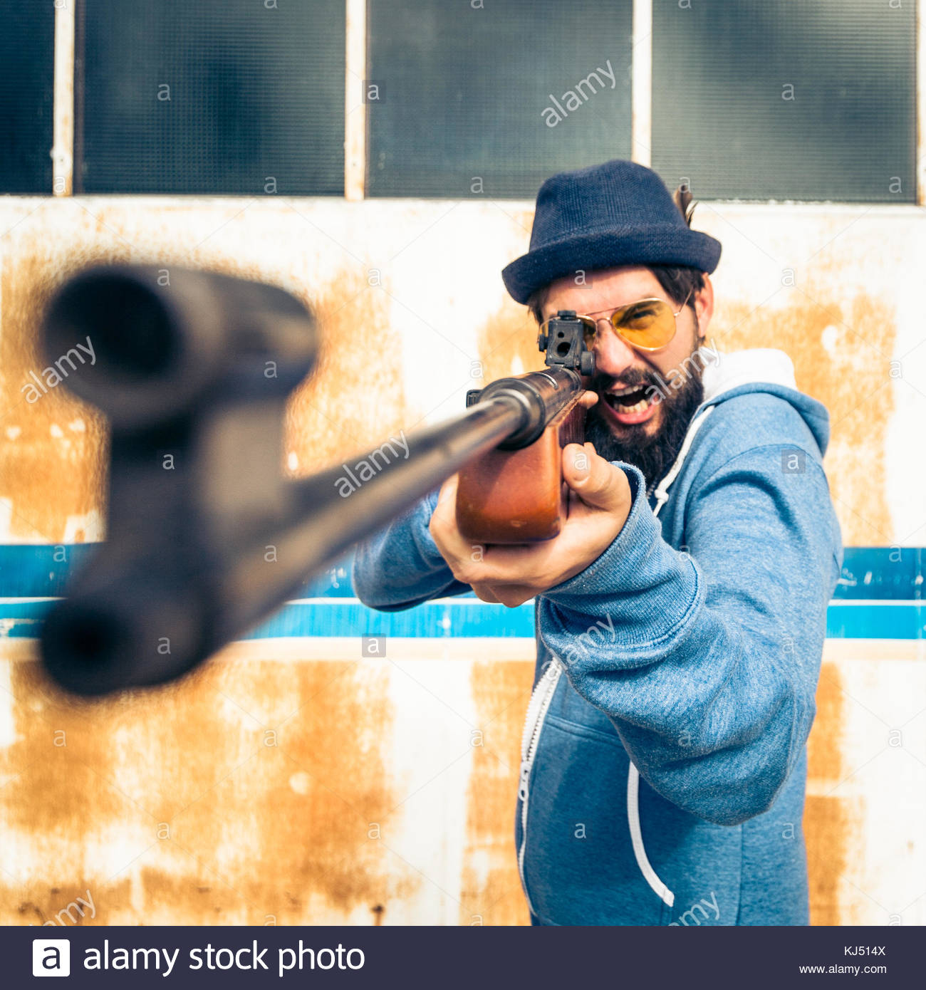 Funny guy pointing the shotgun at a target - Stock Image