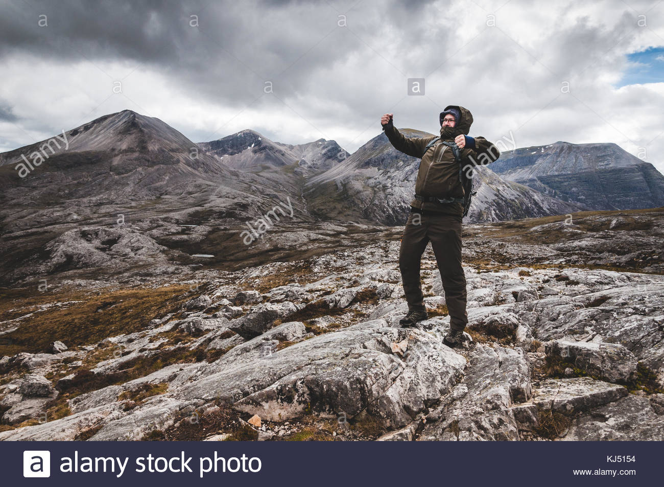 man beating chest on cliff top - Stock Image