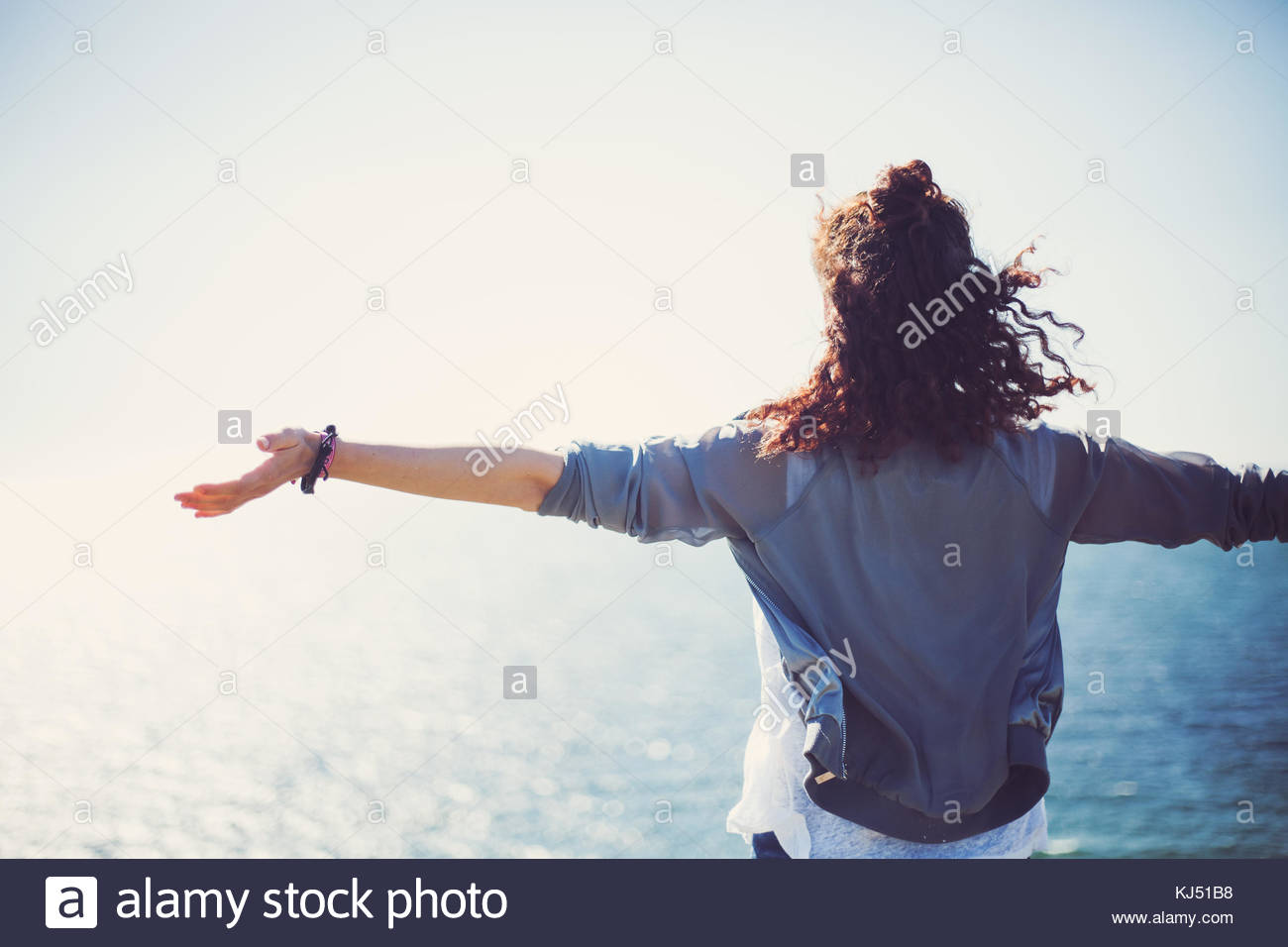 woman arms spread by sea - Stock Image