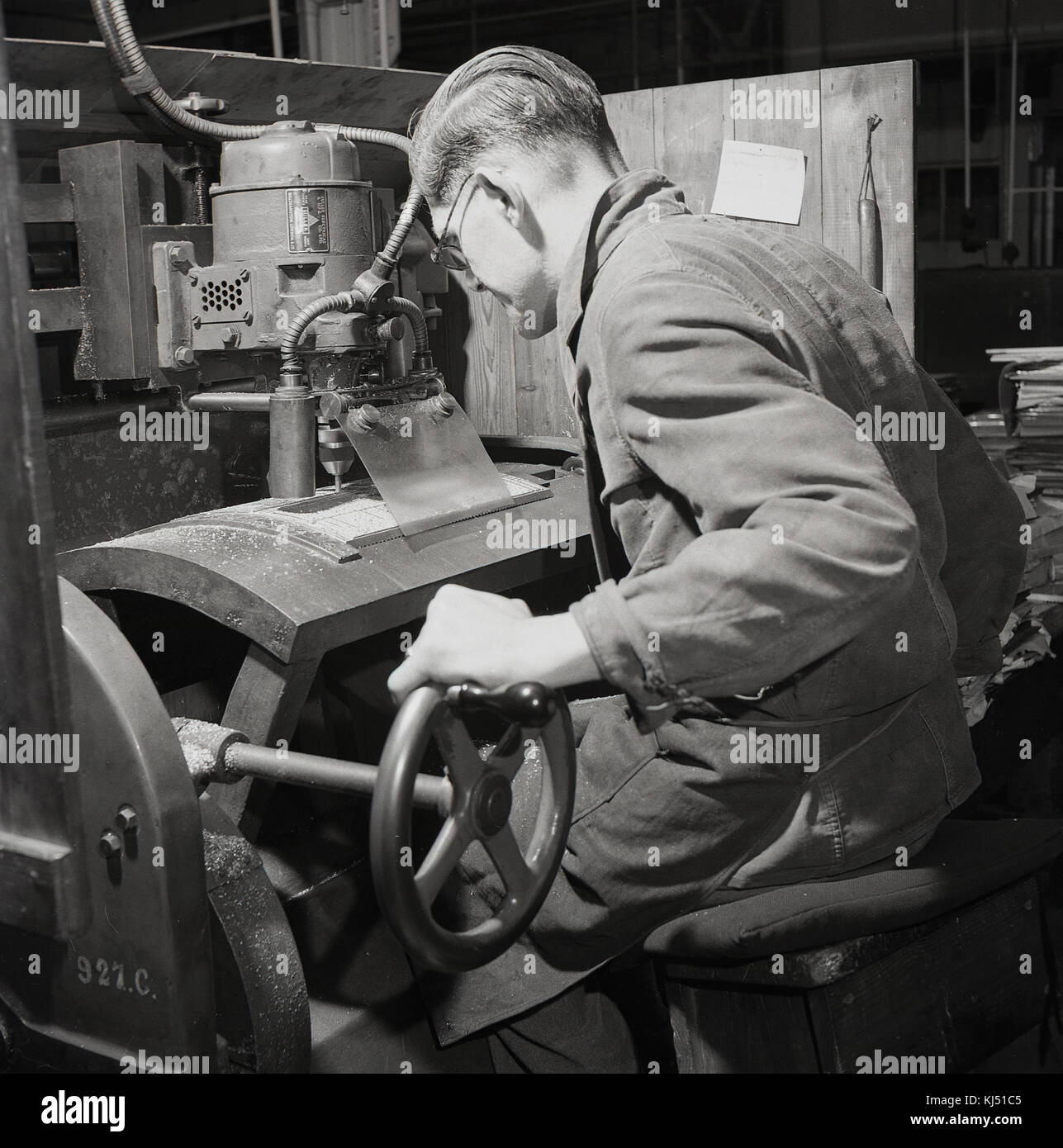1950s, historical, male worker using a Fuller electric motor with drill and wheel to do precision metal  work, England, - Stock Image