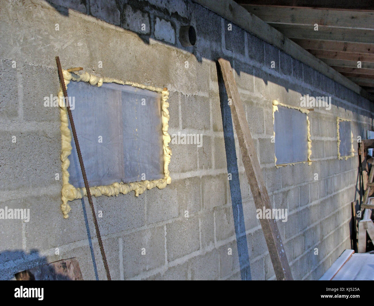 On barn under construction window glass is replaced with plastic film and montage foam. - Stock Image
