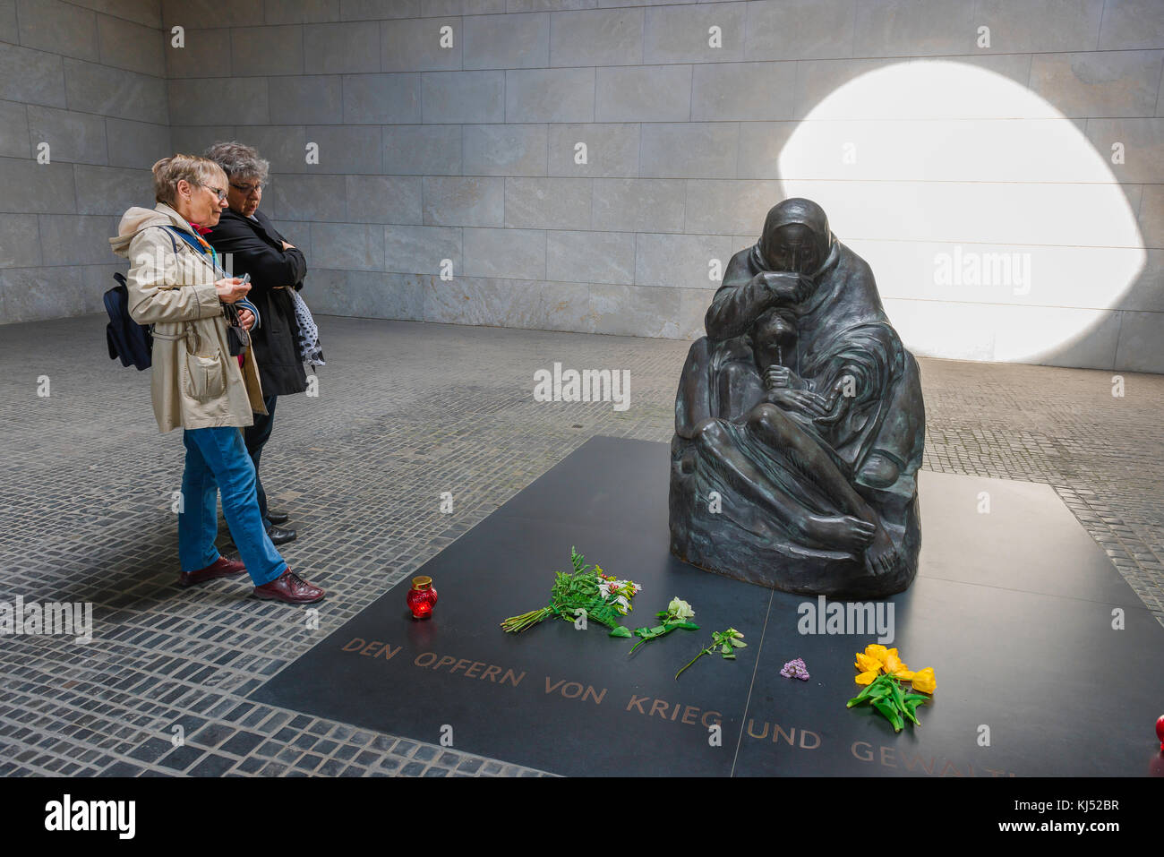 Two women visiting the National Memorial To The Victims Of War And Tyranny in the Neue Wache, Berlin, view a statue - Stock Image