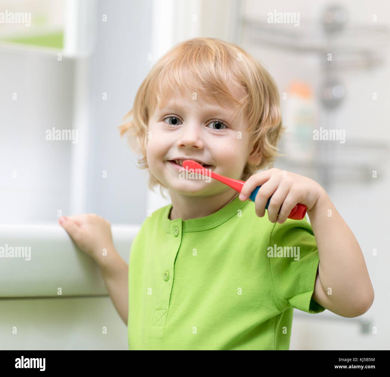 Little boy brushing his teeth in bathroom - Stock Image