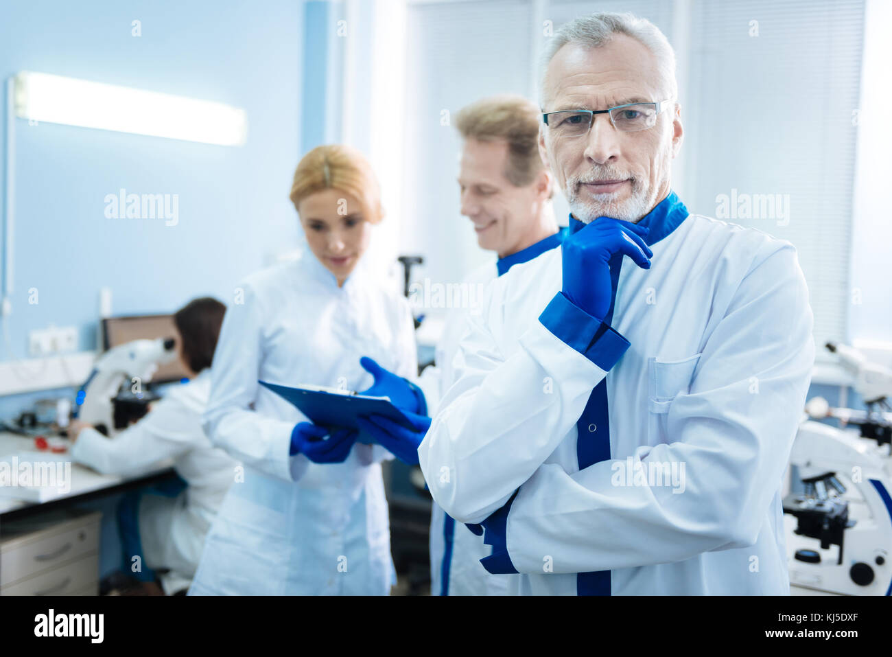 Vigorous grey-haired scientist and others in the background - Stock Image