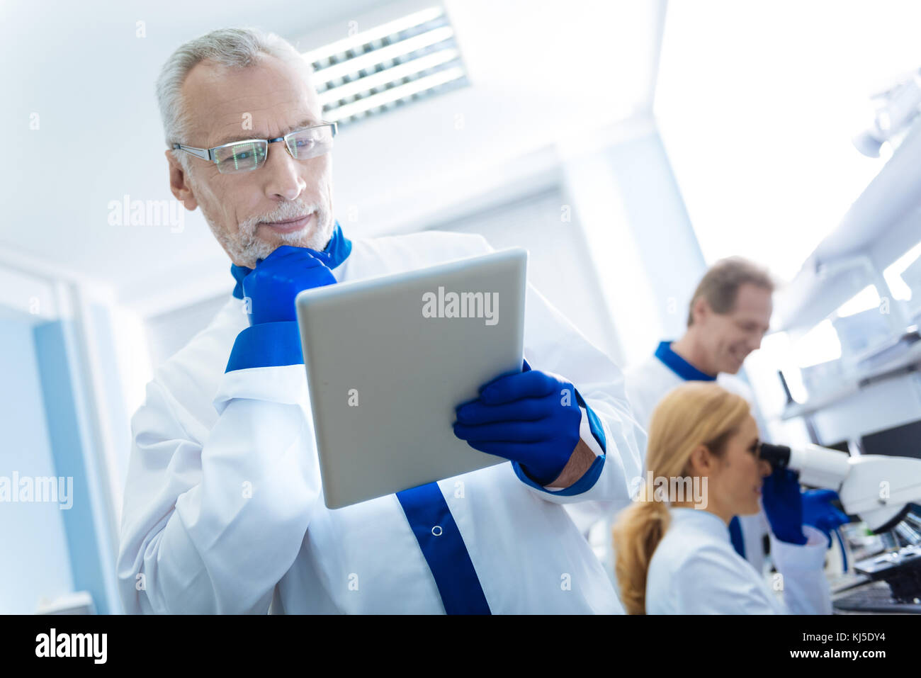 Smiling researcher thinking about gene analysis - Stock Image