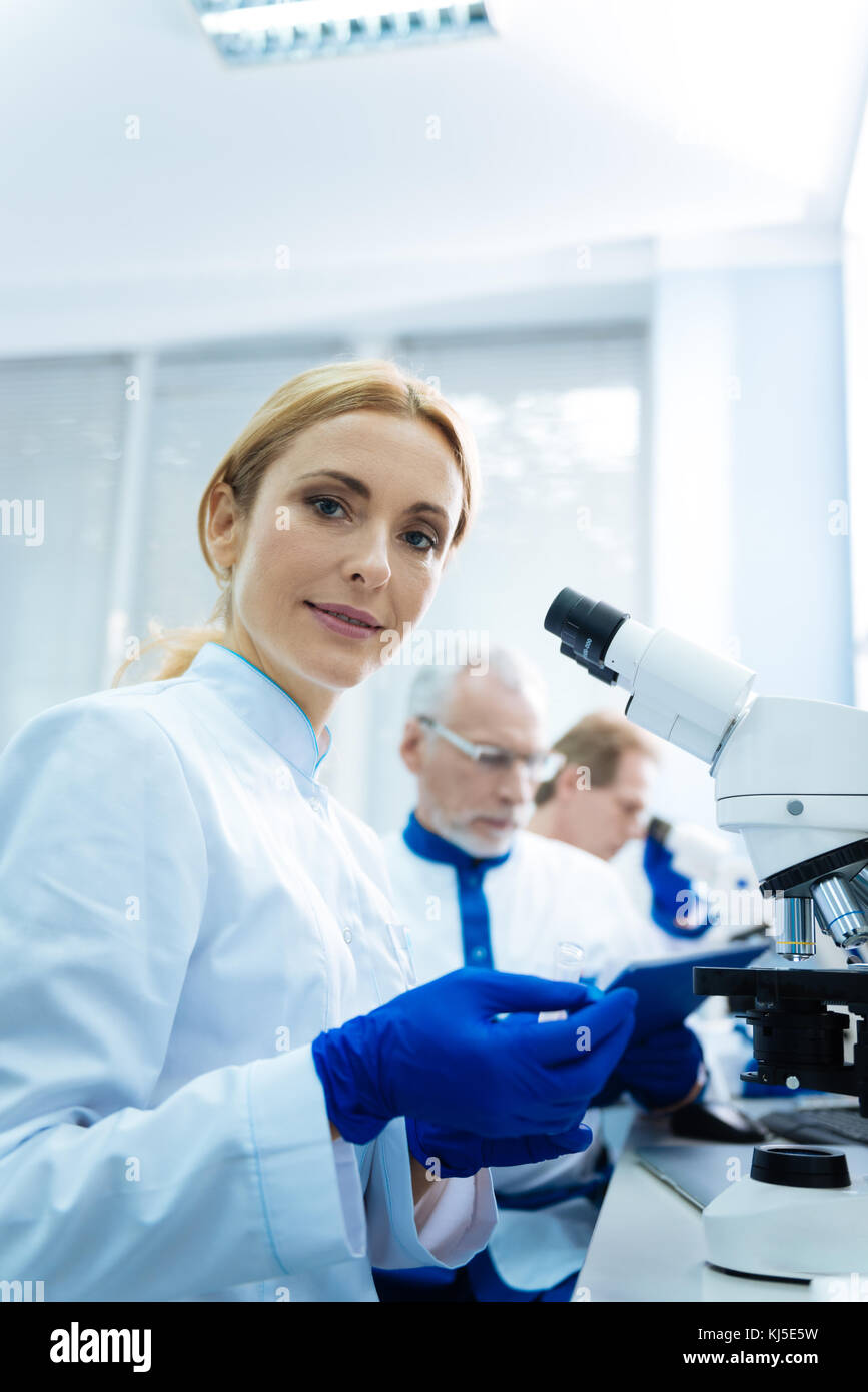 Content scientist sitting at a microscope - Stock Image