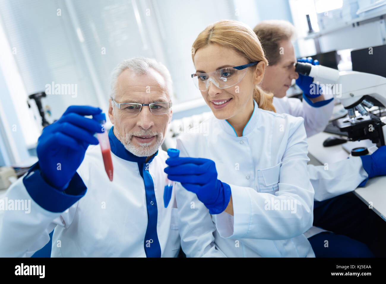 Inspired medical workers holding test tubes - Stock Image