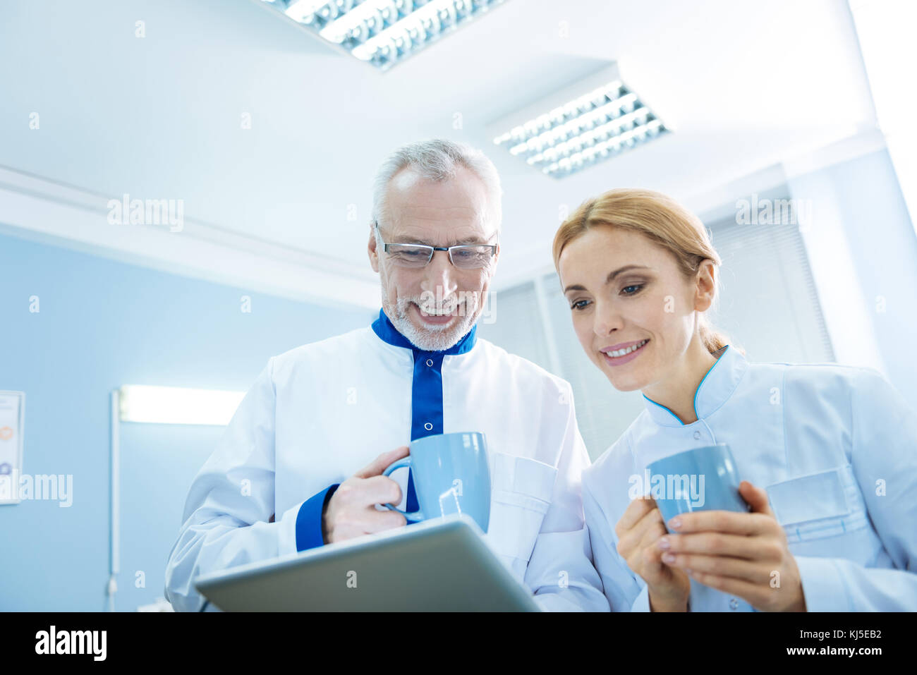 Inspired scientists in uniforms with cups Stock Photo