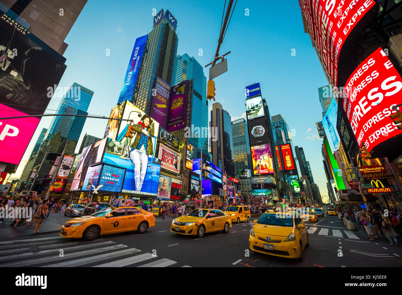 NEW YORK CITY - AUGUST 23, 2017: Bright neon signage flashes over crowds and taxi traffic zooming past Times Square - Stock Image