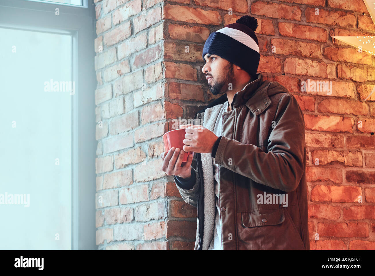 b63c889941e Portrait of bearded Indian hipster male dressed in a warm jacket and a hat