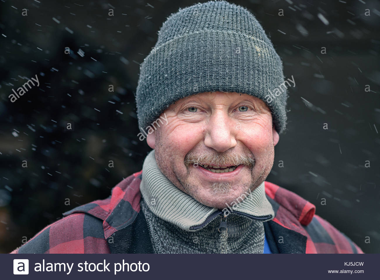 Happy man with a mustache in winter clothing - Stock Image