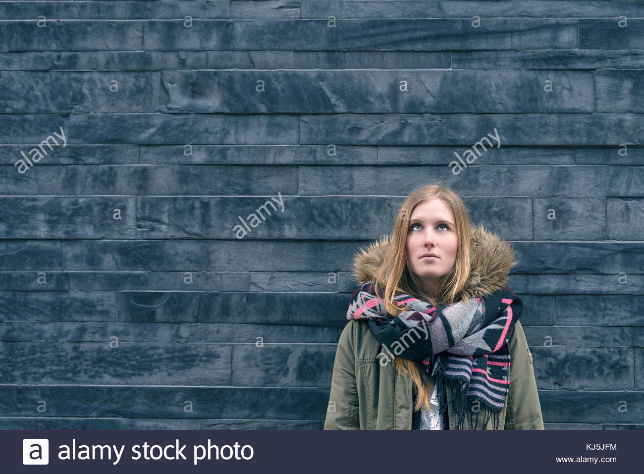 Trendy young student standing thinking - Stock Image