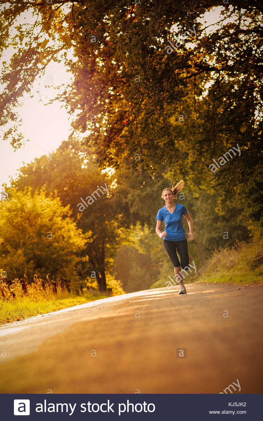 Sporty woman running on a country road - Stock Image