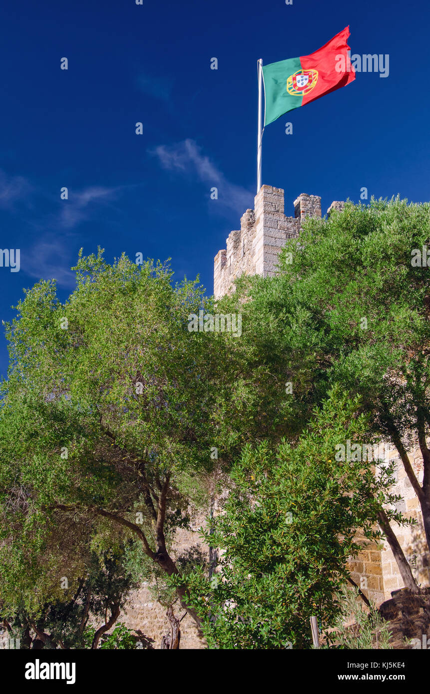 Waving in wind red and green flag of Portugal fixed with flagpole on the walls of old castle called Sao Jorge, located - Stock Image