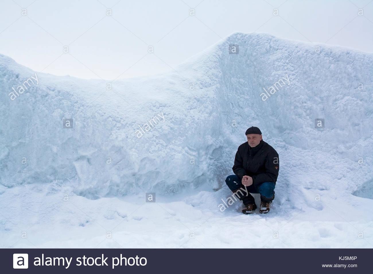 man crouching beside snow drift - Stock Image
