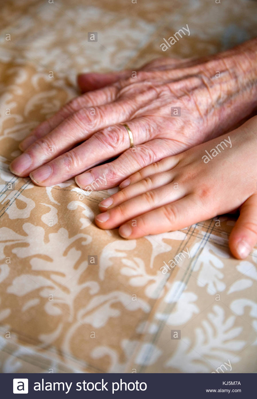 Contrast between old and young hand. Generations - Stock Image