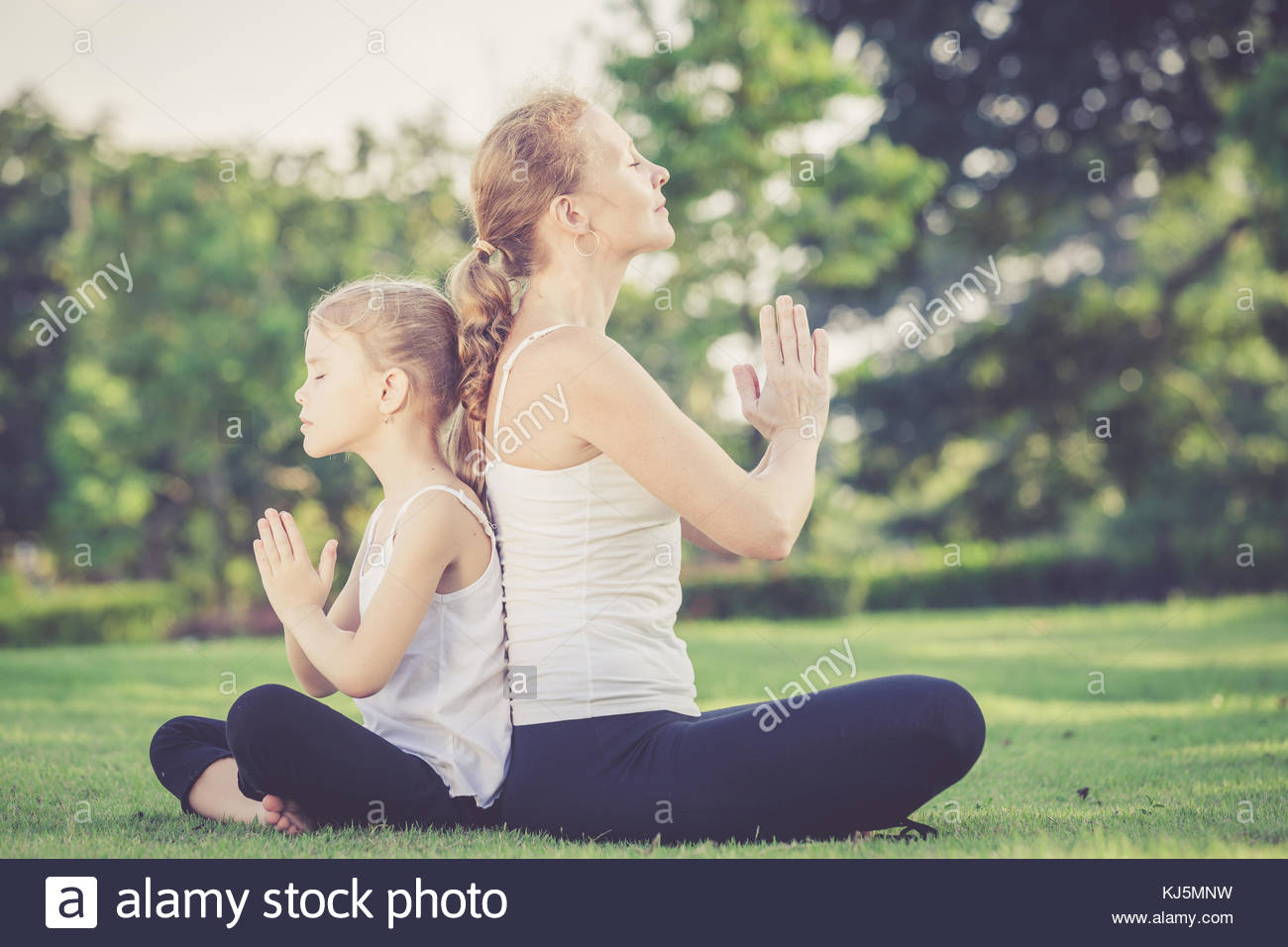 mother and daughter outdoor yoga - Stock Image