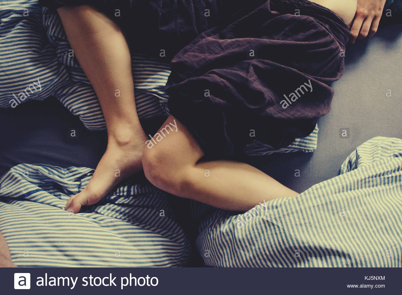 Legs in bed - Stock Image