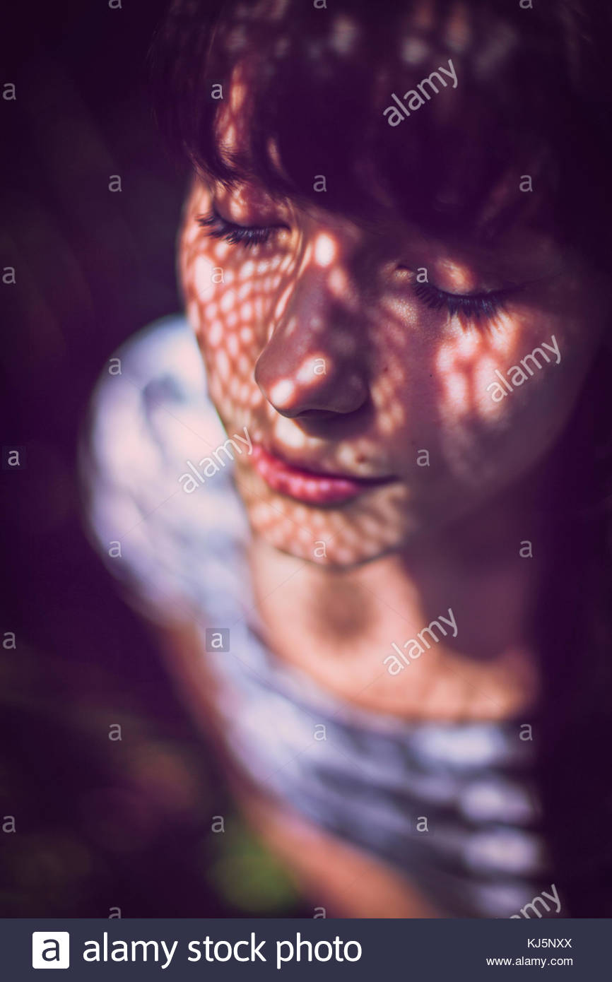Woman with shadow pattern on face - Stock Image