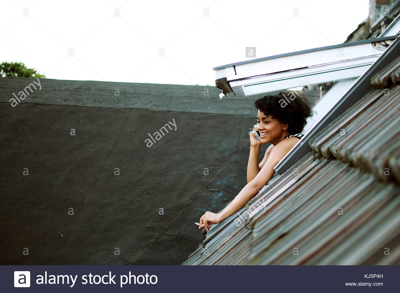 Beautiful woman smokes from the rooftop hatch while talking on the phone - Stock Image